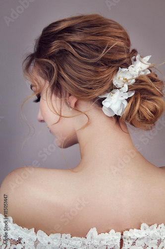 Foto op Canvas Kapsalon Back view of young woman with brown hair in white wedding dress and wreath over gray background