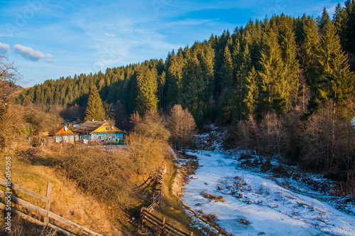 Foto op Canvas Grijze traf. Beautiful view of a frozen river floating through a village and a forest in sunny weather