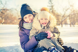 Little girl and her mother playing outdoors at sunny winter day - 185073057