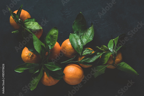 Tangerines with green leaves on dark background. Top view, toned image, moody still life