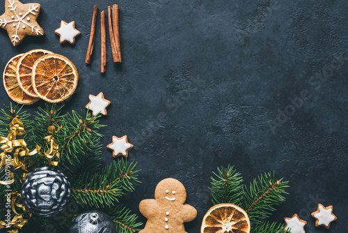 Christmas background with fir tree branch, gingerbread cookies, spices and dried orange rings - 185079676