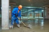concrete floor construction. Worker with screeder - 185087014