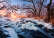 Winter forest with amazing river at sunset. Winter landscape with snowy trees, ice, beautiful frozen river, snowy bushes, colorful sky in dusk. Blurred water. Small waterfalls.Creek with water cascade