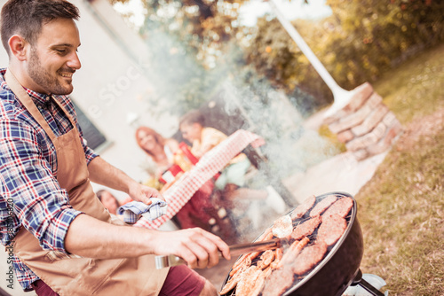 Man preparing barbecue while family having meal in the backyard.