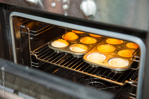 muffins on a baking tray in the oven - 185107262