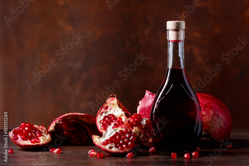 Pomegranate and a bottle of juice. - 185151264