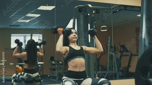 Young sports woman doing exercises with dumbbells in fitness gym. Healthy lifestyle concept © SPY_studio