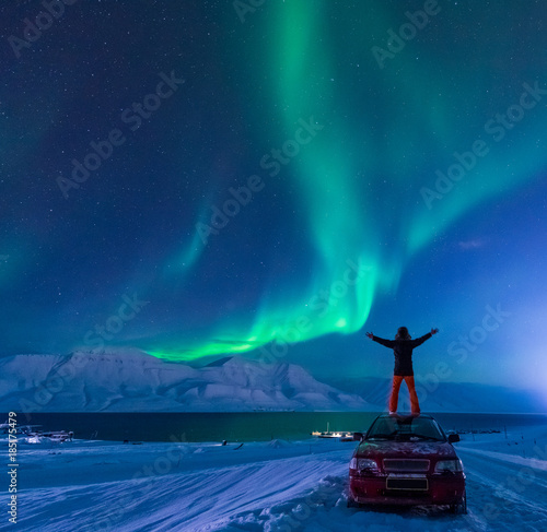 Fotobehang Nachtblauw The polar arctic Northern lights aurora borealis sky star in Norway Svalbard man in Longyearbyen city the moon mountains