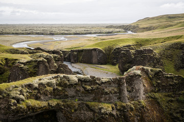 Landscape view of a lava field in the background of green cliffs in Iceland.