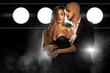 fashioable young couple in love posing and hugging in suit and dress