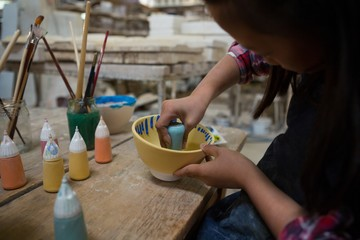 Girl decorating painting bowl