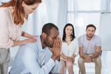 middle aged people supporting upset african american man during anonymous group therapy - 185236062