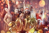 New 2019 Year is coming! Group of cheerful young multiethnic people in Santa hats carrying gold colored numbers and throwing confetti on the party - 185237025
