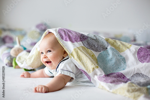 Foto Murales Cute little four month old baby boy, playing at home in bed