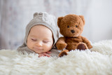 Sweet baby boy in bear overall, sleeping in bed with teddy bear - 185239216