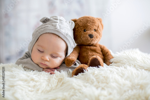 Sweet baby boy in bear overall, sleeping in bed with teddy bear - 185239231
