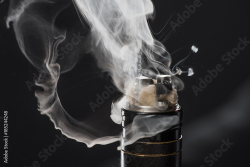 Foto Murales Activating electronic cigarette with clouds of smoke on dark background