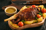 Slow baked lamb leg with potatoes and sauce. - 185247063