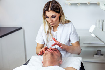Cosmetologist is doing procedure of face massage for young boy / man. Model, close-up. Cosmetological clinic. Healthcare