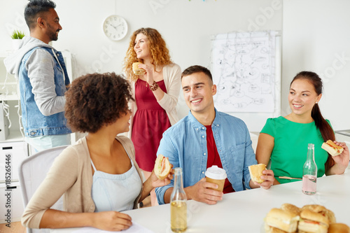 happy friends or team eating at office