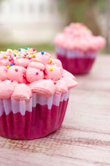 Red velvet cupcake decorated with pink cream on wood background. Warm and pastel color tone.