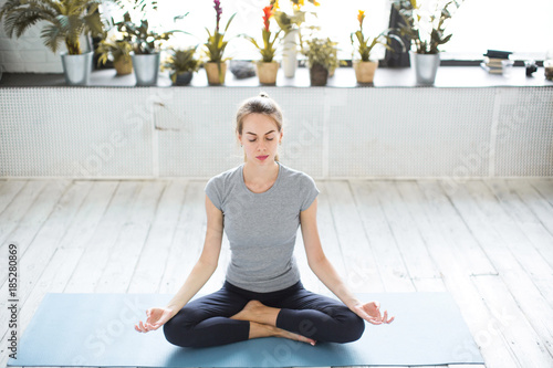 Foto op Aluminium School de yoga Young woman meditates while practicing yoga.