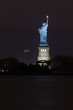 The Statue of Liberty on Ellis Island at night lit by spotlights with an American flag in the wind