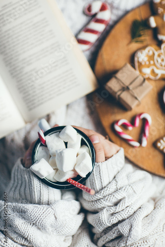 Fotobehang Chocolade Woman holding cup of hot chocolate with marshmallows, reading a book in bed. Winter Christmas theme