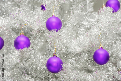 Trendy colored ultraviolet baubles on silver artificial christmas tree
