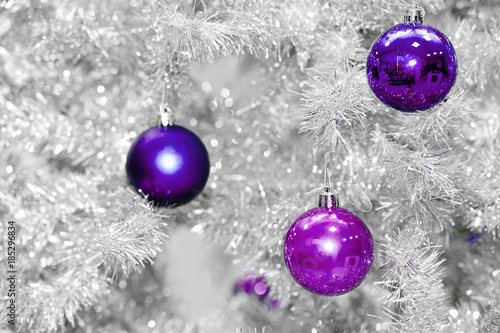 Trendy colored violet or ultraviolet baubles on silver artificial christmas tree