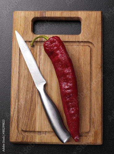 Foto op Canvas Hot chili peppers Hot pepper on the wooden desk with stainless steel knife on dark