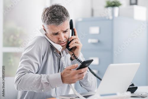 Foto Murales Stressed businessman having multiple calls