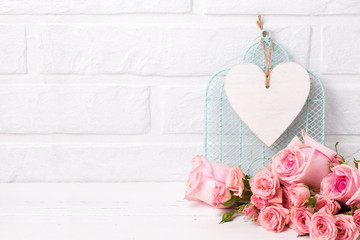 Pink roses flowers and, decorative bird cage and white  heart against  white brick wall.