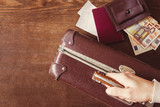 Tourist's hand holding old, leather, suitcase. Brown wallet and euro money with passport and tickets. Historical atmosphere with contemporary banknotes. Vintage style. Traveling or emigration concept. - 185325297