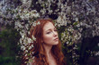 Beautiful happy young woman with red hair enjoying smell in a flowering spring garden