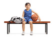 Little basketball player sitting on a wooden bench next to a sports bag