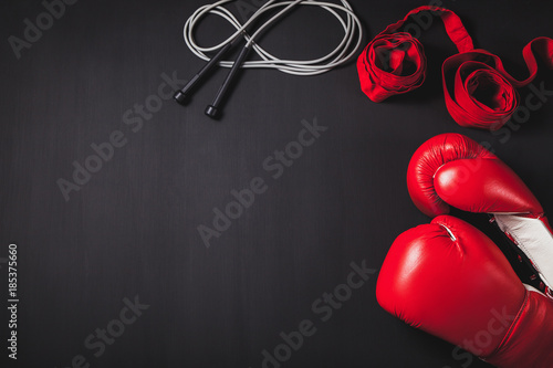 Professional red boxing gloves, wraps, and skipping rope on black background with copy space.