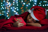 Happy New Year concept. Asian Kids Sleeping and Hold a Gift Box on the Bed with Bokeh Light Background.