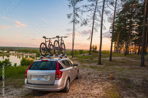 Bike transportation - two bikes on the roof of a car. Sunset. - 185385442