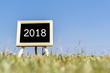 Chaik board on grass field with 2018
