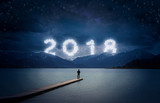 New year background, young man standing on a jetty in a lake and looking to the mountains under the dark sky with cloudy text 2018 - 185390895