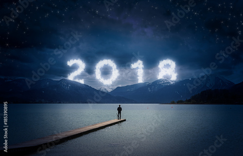 Aluminium Pier New year background, young man standing on a jetty in a lake and looking to the mountains under the dark sky with cloudy text 2018