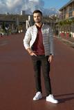Jeune homme barbu au pantalon troué photographie de plein pied - 185402068
