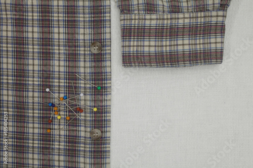 Poster checkered shirt and pins on a tailor's table, copy space