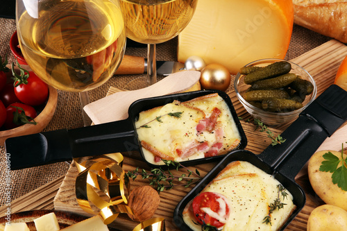 Delicious traditional Swiss melted raclette cheese on diced boiled or baked potato served in individual skillets. - 185406840