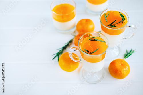 Foto op Plexiglas Sap Tangerine panna cotta dessert with rosemary in wineglasses