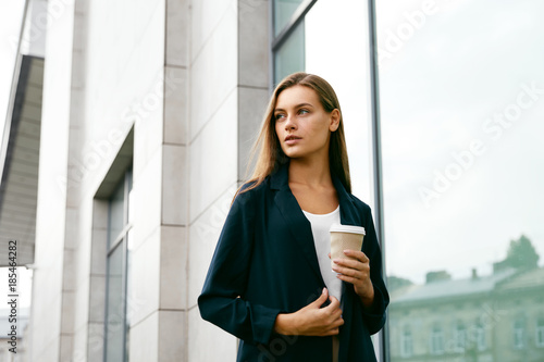Beautiful Woman With Cup Of Coffee Walking On Street.