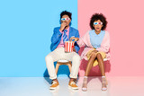 young african american couple sitting on chairs and eating popcorn against pink and blue wall - 185477830