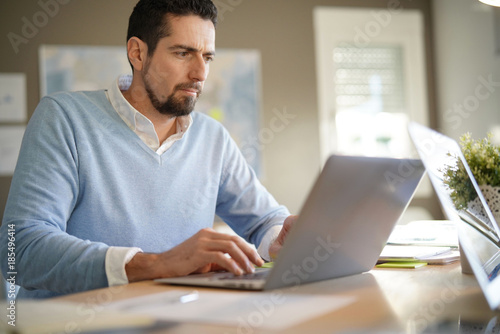 Man in office working on laptop computer