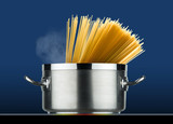 steel pot with spaghetti cooking on induction plate  - 185497603
